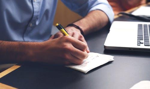Uma pessoa de frente ao computador e fazendo anotações em um papel